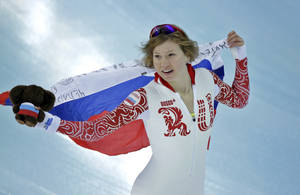 Photo - Silver medallist Russia's Olga Fatkulina holds her national flag and celebrates after the women's 500-meter speedskating at the Adler Arena Skating Center during the 2014 Winter Olympics, Tuesday, Feb. 11, 2014, in Sochi, Russia. (AP Photo/David J. Phillip )