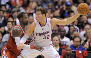 Photo - Clippers power forward Blake Griffin, right, keeps the ball away from Milwaukee Bucks shooting guard Stephen Jackson during the first half of their NBA basketball game, Saturday, Jan. 7, 2012, in Los Angeles.  (AP Photo/Mark J. Terrill)