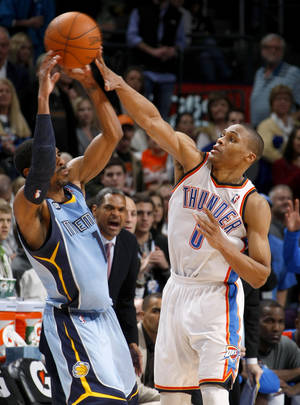 Photo - Oklahoma City's Russell Westbrook (0) defends Memphis' Mike Conley (11) during the NBA game between the Oklahoma City Thunder and the Memphis Grizzlies at Chesapeake Energy Arena in Oklahoma CIty, Friday, Feb. 3, 2012. Photo by Bryan Terry, The Oklahoman