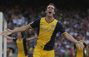 Photo - Atletico's Diego Godin from Uruguay, celebrates after scoring his side's first goal during a Spanish La Liga soccer match between FC Barcelona and Atletico Madrid at the Camp Nou stadium in Barcelona, Spain, Saturday, May 17, 2014. (AP Photo/Andres Kudacki)