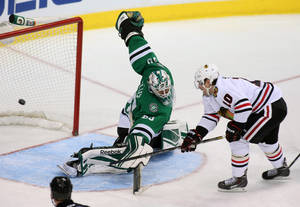 Photo - Dallas Stars goalie Dan Ellis (30) gives up a goal to Chicago Blackhawks left wing Patrick Sharp (10) in the second period of an NHL hockey game Tuesday, Dec. 10, 2013, in Dallas, Texas. (AP Photo/Sharon Ellman)