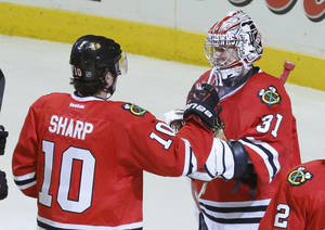 Photo - Chicago Blackhawks left wing Patrick Sharp (10) celebrates with goalie Antti Raanta the Blackhawks' 7-2 win over the Philadelphia Flyers after an NHL hockey game Wednesday, Dec. 11, 2013, in Chicago. (AP Photo/Charles Rex Arbogast)