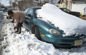 Photo - Ingrid Parham chisels away at frozen snow surrounding her car, Sunday, Feb. 16, 2014, in Paterson, N.J., on in preparation for work on Monday. (AP Photo/Northjersey.com, Amy Newman) ONLINE OUT; MAGS OUT; TV OUT; INTERNET OUT;  NO ARCHIVING; MANDATORY CREDIT.