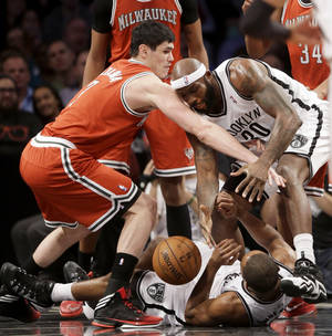 Photo - Milwaukee Bucks' Ersan Ilyasova, left, fights for a rebound with Brooklyn Nets' Reggie Evans, right, and Alan Anderson, bottom, during the first half of an NBA basketball game at the Barclays Center, Friday, Dec. 27, 2013, in New York. (AP Photo/Seth Wenig)