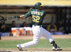 Photo -   Oakland Athletics' Yoenis Cespedes swings for an RBI triple off Seattle Mariners' Erasmo Ramirez in the first inning of a baseball game Sunday, Sept. 30, 2012, in Oakland, Calif. (AP Photo/Ben Margot)