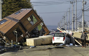 Photo - This March 12, 2011 file photo a man walks by a collapsed house and debris at Sendai Port in Sendai, northeastern Japan, following Friday's 8.9-magnitude quake.  New research appearing Thursday July 11, 2013 in the journal Science suggests that such powerful distant quakes can trigger minor shaking around wastewater injection sites in the U.S. Midwest. (AP Photo/Koji Sasahara,File)