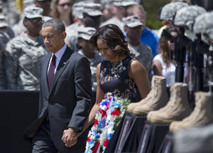 Photo - President Barack Obama and first lady Michelle Obama arrive for a memorial ceremony, Wednesday, April 9, 2014, at Fort Hood Texas, for those killed there in a shooting last week. President Barack Obama is reprising his role as chief comforter as he returns once again to a grief-stricken corner of America to mourn with the families of those killed last week at Fort Hood and offer solace to the nation.(AP Photo/Carolyn Kaster)