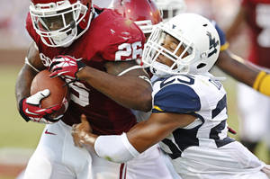 Photo - Oklahoma's Damien Williams (26) is stopped short of the goal line by West Virginia's Darwin Cook (25) in the second quarter of an NCAA college football game in Norman, Okla., Saturday, Sept. 7, 2013. (AP Photo/Sue Ogrocki)