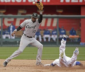 Photo - Kansas City Royals' Lorenzo Cain, right, beats the tag by Chicago White Sox shortstop Alexei Ramirez (10) to steal second during the fifth inning of a home opener baseball game Friday, April 4, 2014, in Kansas City, Mo. (AP Photo/Charlie Riedel)