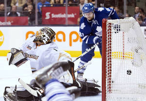 Photo - Toronto Maple Leafs forward Phil Kessel, right, scores past Anaheim Ducks goalie Jonas Hiller, left, during the second period of an NHL hockey game in Toronto on Tuesday, Oct. 22, 2013. (AP Photo/The Canadian Press, Nathan Denette)