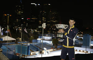 photo - Serbia's Novak Djokovic poses for photographers as he holds his trophy aloft after defeating Britain's Andy Murray in the men's final at the Australian Open tennis championship in Melbourne, Australia, Monday, Jan. 28, 2013.  (AP Photo/Andy Wong)