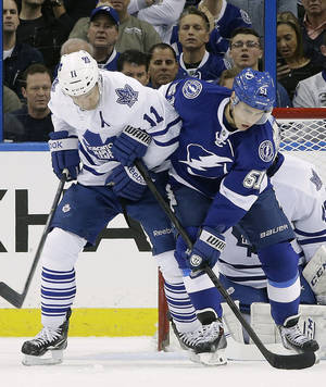 Photo - Toronto Maple Leafs center Jay McClement (11) ties up Tampa Bay Lightning center Valtteri Filppula (51), of Finland, in front of the goal during the first period of an NHL hockey game, Thursday, Feb. 6, 2014, in Tampa, Fla. (AP Photo/Chris O'Meara)