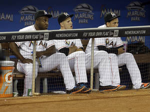 Photo - Miami Marlins starting pitcher Jose Fernandez, center, sits in the dugout with teammates Marcell Ozuna, left, during a baseball game against the Atlanta Braves, Thursday, Sept. 12, 2013, in Miami. Fernandez pitched his last game of the season Wednesday. (AP Photo/Lynne Sladky)