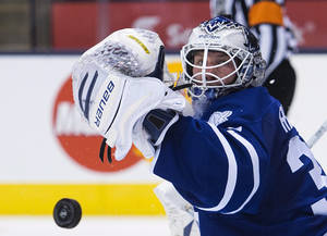 Photo - Toronto Maple Leafs goalie James Reimer makes a save against the Ottawa Senators during the first period of an NHL preseason hockey game in Toronto on Tuesday, Sept. 24, 2013. (AP Photo/The Canadian Press, Nathan Denette)