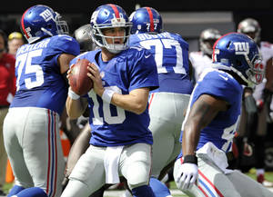 photo -   New York Giants quarterback Eli Manning (10) looks to pass as teammates Sean Locklear (75) and Kevin Boothe (77) block during the first half of an NFL football game against the Tampa Bay Buccaneers Sunday, Sept. 16, 2012, in East Rutherford, N.J. Manning threw for 510 yards, second most for a Giants quarterback, and Andre Brown's 2-yard run with 31 seconds left lifted New York to a wild 41-34 victory Sunday over the Tampa Bay Buccaneers. (AP Photo/Bill Kostroun)
