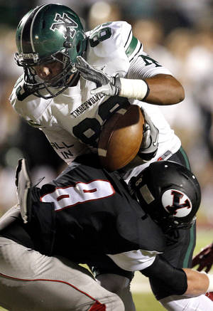 Photo - Yukon's Nick Bryant tackles Norman North's Payton Prince during a high school football game between Yukon and Norman North in Yukon, Okla.,   Friday, Oct. 4, 2013. Photo by Sarah Phipps, The Oklahoman
