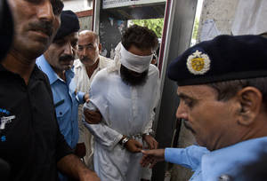 Photo -   Pakistani police officers escort blindfolded Muslim cleric Khalid Chishti to appear in court in Islamabad, Pakistan, Sunday, Sept. 2, 2012. In the latest twist in a religiously charged case that has focused attention on the country's harsh blasphemy laws, Pakistani police arrested Chishti who they say planted evidence in the case of a Christian girl accused of blasphemy. (AP Photo/Anjum Naveed)