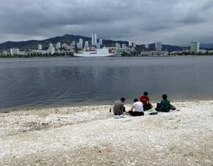 Photo - In this Sunday, June 22, 2014 photo taken with smartphone camera, North Koreans have a picnic in a beach with a ferry Mangyongbong-92 anchored, in the background in Wonsan, North Korea. Wonsan, a sleepy port on North Korea's east coast, is gearing up for a busy summer - and, if talks with Japan go as North Korea hopes, maybe a return to livelier days. (AP Photo/Eric Talmadge)