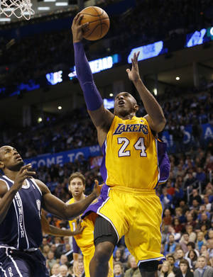 Photo - Los Angeles Lakers Kobe Bryant (24) shoots in front of Oklahoma City Thunder forward Serge Ibaka (9) in the second quarter of an NBA basketball game in Oklahoma City, Friday, Dec. 13, 2013. (AP Photo/Sue Ogrocki)