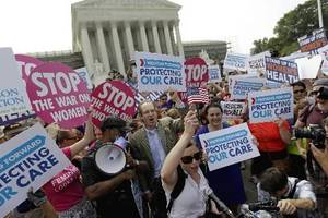 Photo - Supporters of President Barack Obama's health care law celebrate outside the Supreme Court in Washington, Thursday, June 28, 2012, after the court's ruling. AP Photo/ David Goldman)