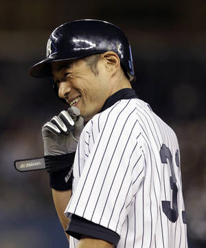 Photo -   New York Yankees Ichiro Suzuki smiles at first base after driving in the winning run against the Toronto Blue Jays in the eighth-inning of the Yankees' 2-1 victory in Game 2 of a baseball doubleheader at Yankee Stadium in New York, Wednesday, Sept. 19, 2012. (AP Photo/Kathy Willens)