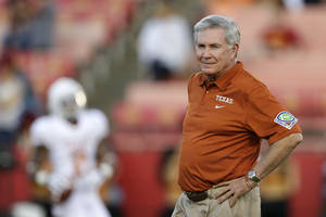 Photo - Texas head coach Mack Brown watches his team warm up before an NCAA college football game against Iowa State, Thursday, Oct. 3, 2013, in Ames, Iowa. (AP Photo/Charlie Neibergall)