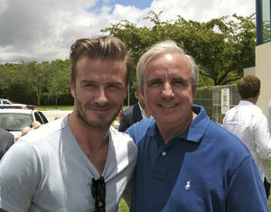 Photo - In this undated photo released by Miami-Dade County, former soccer star David Beckham poses for a photo with Miami-Dade County Mayor Carlos Gimenez, in Miami. Beckham may be setting his sights on a new sports venture: A professional soccer team in Miami. The newly retired Beckham toured Sun Life and Florida International University stadiums and met with Miami-Dade County Mayor Carlos Gimenez on Saturday. (AP Photo/Miami-Dade County)