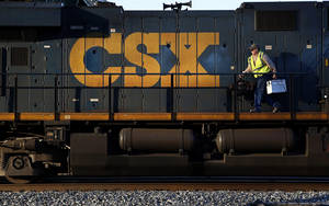 Photo - In this March 22, 2014 picture, a crew member walks on a CSX freight train engine in Brunswick, Md. CSX Corp. reports quarterly earnings after the market close on Tuesday, April 15, 2014. (AP Photo/Patrick Semansky)