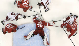 Photo - Detroit Red Wings goalie Jimmy Howard (35) covers the puck against the Phoenix Coyotes in the second period of an NHL hockey game in Detroit, Monday, April 22, 2013. Detroit won 4-0. (AP Photo/Paul Sancya)