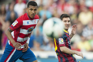 Photo - Barcelona's Lionel Messi from Argentina, right, in action with Granada's Jeison Murillo from Colombia during a Spanish La Liga soccer match between FC Granada and FC Barcelona at Los Carmenes stadium in Granada, Spain, Saturday, April 12, 2014. (AP Photo/Daniel Tejedor)