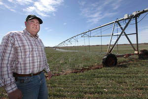 Photo -  Above: Battling a drought that dates to October 2010, T.J. Beach, of Elmer, relies on using a private well to pump water for center pivot irrigation on a wheat field. He is irrigating much less than in the past, but Beach feels fortunate because many farmers have been unable to irrigate at all for some time. Photos by  David McDaniel, The Oklahoman  <strong>David McDaniel - The Oklahoman</strong>