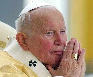 photo - Pope John Paul II prays during an outdoor mass in central Slovakia in 2003. <strong>RENE MIKO - AP</strong>