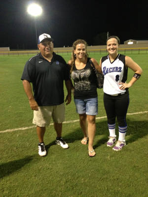 Photo - Newcastle softball coach Mike Crossley, left, poses with the catcher from his first win, Misti Gravatt, center, and her daughter, Allyson LeClaire, who played right field in his 800th win. Photo provided