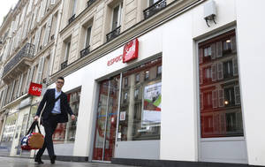 Photo - A man walks past a SFR shop in Paris, Tuesday March 18, 2014. France's Vivendi has decided to start exclusive negotiations with media company Altice, the holding company for Numericable, over the possible sale of its unit SFR, France's No. 2 mobile phone operator. The move is a blow for Bouygues, a conglomerate that had made a competing offer and raised it to 11.3 billion euros ($15.8 billion) this week. (AP Photo/Jacques Brinon)