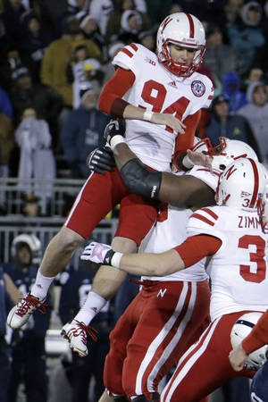 Photo - ADVANCE FOR FRIDAY, DEC. 27 - FILE -  In this Nov. 23, 2013, file photo, Nebraska kicker Pat Smith (94) celebrates with teammates after kicking the game-winning field goal in overtime to beat Penn State 23-20 in an NCAA college football game in State College, Pa. Smith calls himself a risk taker. It's how he explains why, after his junior season, he gave up his scholarship and starting job at Western Illinois to walk on and compete to be Nebraska's kicker for one season. (AP Photo/Gene J. Puskar, File)