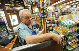 Photo - File - In this Aug. 24, 2013 file photo, Pinecrest General Store owner Dan Vaughn stands in his empty business in Pinecrest, Calif. Vaughn says that business is down 90% from normal at this time of year as a result of the Rim Fire which continues to burn in the Stanislaus National Forest.  Vaughn sent four of his employees home due to the lack of business. It doesn't pay to be a dateline in a disaster story, as the folks around Groveland, Calif. will tell you. On what would have been the busiest weekend of the summer had the Strawberry Music Festival not been cancelled, hotel rooms are empty and the local coffee roaster got rid of all 6 employees because the road to Yosemite is closed. One hotelier has had $20,000 in cancellations just this week. In the park, tourists are enjoying elbow room as hard-to-get campsite and lodging rooms are full but day tourists are staying away out of fear of fire and smoke. (AP Photo/The Modesto Bee, Elias Funez, File)