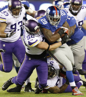 Photo - Minnesota Vikings outside linebacker Chad Greenway, left, tackles New York Giants running back Michael Cox (29) during the first half of an NFL football game Monday, Oct. 21, 2013 in East Rutherford, N.J. (AP Photo/Julio Cortez)