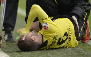 Photo - Dortmund's Jakub Blaszczykowski of Poland is injured on the ground and has to leaves the stadium during the German Bundesliga soccer match between Borussia Dortmund and FC Augsburg in Dortmund,  Germany, Saturday, Jan. 25, 2014. (AP Photo/Martin Meissner)