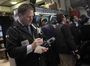 Photo - Trader Thomas McCauley, left, works on the floor of the New York Stock Exchange Thursday, Dec. 6, 2012.  The U.S. stock market wobbled between small gains and losses in early trading Thursday. (AP Photo/Richard Drew)