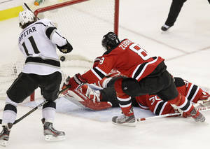 Photo -   Los Angeles Kings' Anze Kopitar, left, of Slovenia, scores past New Jersey Devils' Martin Brodeur, bottom, and Dainius Zubrus, of Lithuania, during overtime in Game 1 of the NHL hockey Stanley Cup finals Wednesday, May 30, 2012 in Newark, N.J. The Kings won 2-1. (AP Photo/Kathy Willens)