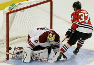 Photo - Chicago Blackhawks' Brandon Pirri (37) scores against Phoenix Coyotes goalie Mike Smith in a shootout during an NHL hockey game in Chicago, Thursday, Nov. 14, 2013. The Blackhawks won 5-4. (AP Photo/Nam Y. Huh)