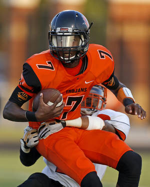 Photo - Patrick McKaufman of Douglass is brought down by Booker T. Washington's Ross Stovall during their high school football game at Douglass in Oklahoma City, Friday, September 6, 2013. Photo by Bryan Terry, The Oklahoman