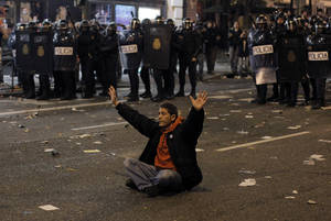Photo -   A protestor sits in front of the riot police riot to stop the clashes during a general strike in Madrid, Spain, Wednesday, Nov. 14, 2012. Spain's main trade unions stage a general strike, coinciding with similar work stoppages in Portugal and Greece, to protest government-imposed austerity measures and labor reforms. The strike is the second in Spain this year. (AP Photo/Andres Kudacki)
