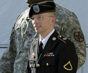 photo - FILE - Army Pfc. Bradley Manning, right, is escorted out of a courthouse in Fort Meade, Md., Monday, June 25, 2012, after a pretrial hearing. The U.S. Army private charged with sending thousands of classified documents to the WikiLeaks secrets-sharing website faces a pretrial hearing Tuesday, Jan. 8, 2013 about whether his motivation matters in the largest leak of classified material in the country's history. (AP Photo/Patrick Semansky)