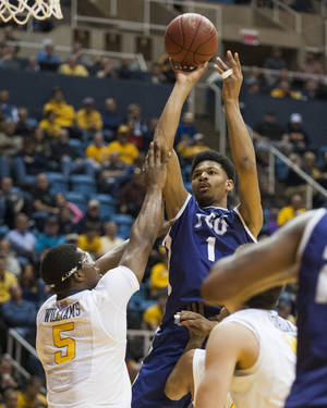 Photo - TCU's Karviar Shepherd, right, looks to shoot over West Virginia's Devin Williams during the first half of an NCAA college basketball game Saturday, March 1, 2014, in Morgantown, W.Va. (AP Photo/Andrew Ferguson)