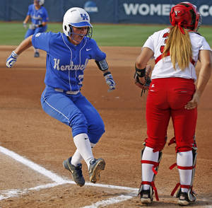 Photo - Kentucky's Nikki Sagermann (77)  celebrates as she score behind La.-Lafayette's Lexie Elkins (33) during a Women's College World Series game between La.-Lafayette and Kentucky at ASA Hall of Fame Stadium in Oklahoma City Thursday, May 29, 2014. Photo by Bryan Terry, The Oklahoman