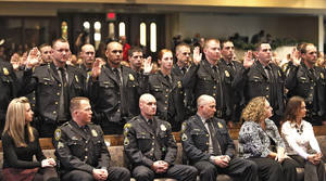 Photo - Oklahoma City Police Department graduates take the oath of office Thursday during their graduation ceremony at First United Methodist Church. The department graduated 38 police recruits in the ceremony. See more photos on Page 14A.  PHOTO BY DAVID MCDANIEL, The Oklahoman