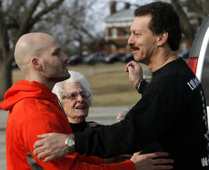 Photo - Left:  Michael Behenna is hugged Friday by his father, Scott Behenna, as his grandmother, Betty Zemp, looks on after his release from prison at Fort Leavenworth, Kan.  Photos by Sarah Phipps,  The Oklahoman <strong>SARAH PHIPPS -   </strong>