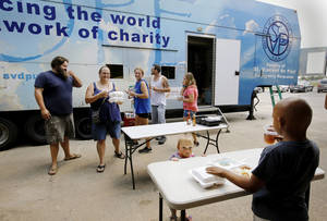 "Photo - Individuals eat a free meal after they receive their household items as part of a recent disaster assistance effortcalled ""House in a Box."" in Oklahoma City.  <strong>Jim Beckel - THE OKLAHOMAN</strong>"