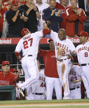 Photo -   Los Angeles Angels' Mike Trout, left, and Erick Aybar celebrate Trout's home run against the Los Angeles Dodgers in the fourth inning of a baseball game in Anaheim, Calif., Friday, June 22, 2012. (AP Photo/Jae C. Hong)